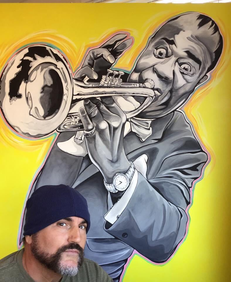 Artist Don Kobasky posing next to Louis Armstrong Painting